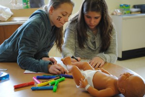 Seventh-graders Emma & Kayla took the challenge of improving their classroom's infant simulator seriously.